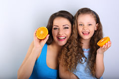 Enjoying fun young mother and cute long hair daughter holding sl Stock Images