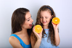 Enjoying fun young mother showing her cute long hair daughter th Royalty Free Stock Image