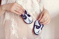 Enjoying future life. Pregnant woman holding small baby booties at her belly, closeup stock photo