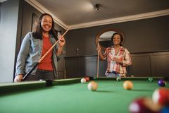 Enjoying a Game of Pool. Two mid adult friends playing a game of pool in a games room in a house stock images