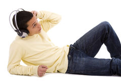 Enjoying good music. Young man lie down on the floor relaxing at the sound of good music Stock Photography