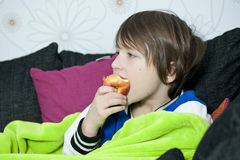 Enjoying healthy snack. Young boy in sofa eating an apple Stock Photo