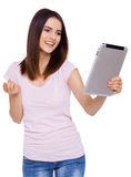 Enjoying her new digital tablet. Beautiful cheerful young woman using her tablet with smile while standing over white background Stock Photography