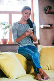 Enjoying her new mobile phone. Beautiful young woman holding smart phone and looking at it with smile while sitting on the couch at home Stock Photography