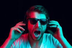 Enjoying his favorite music. Happy young stylish man in sunglasses with headphones listening sound and smiling while standing against blue neon background stock images