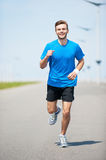 Enjoying his daily jog. Full length front view of handsome young man running along the road and smiling Royalty Free Stock Photo