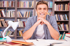 Enjoying his time in library. Handsome young man leaning his face on hands and smiling while sitting at the desk in library Royalty Free Stock Photos