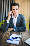 Enjoying his work. Happy young businessman talking on the mobile phone in front notebook while sitting at his working place Royalty Free Stock Images