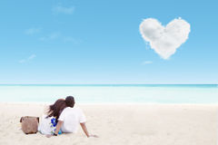 Enjoying honeymoon at white sand beach. With love cloud Royalty Free Stock Images