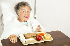Enjoying Hospital Food. Senior hospital patient eating her lunch on a tray Royalty Free Stock Images
