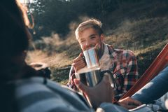 Enjoying hot coffee. Happy young couple having morning coffee wh. Ile camping in mountains Royalty Free Stock Photos