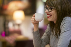 Enjoying a hot drink. Beautiful young woman enjoying a hot drink with friends in a cosy cafe Stock Image