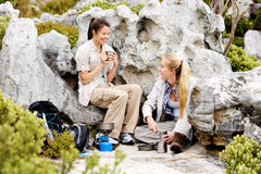 Enjoying a hot drink after a cold days hike. Two camping women sitting together enjoying a nice hot drink royalty free stock photography