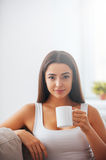 Enjoying hot and fresh coffee. Beautiful young woman holding coffee cup and looking at camera while sitting on the couch at home Stock Photos