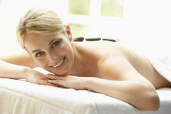 enjoying hot stone treatment woman young Royaltyfri Bild