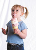 Enjoying Ice Cream. A little girl taking a big bite of ice cream Royalty Free Stock Images