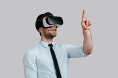 Enjoying innovative technologies. Good looking young man in virtual reality headset pointing in the air while standing against grey background Stock Image