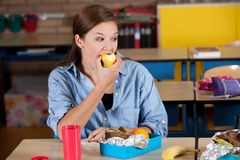 Enjoying a juicy apple. Young student enjoying a tasty apple in the class room Stock Images