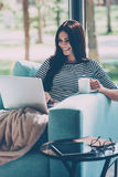 Enjoying leisure time at home. Beautiful young smiling woman working on laptop and drinking coffee while sitting in a big comfortable chair at home Royalty Free Stock Photo