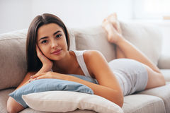 Enjoying leisure time at home. Beautiful young woman holding hand on hair and looking at camera while lying on the couch at home Stock Photography