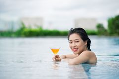 Enjoying leisure time. Young Asian woman with a cocktail enjoying her leisure time in the swimming pool Royalty Free Stock Images
