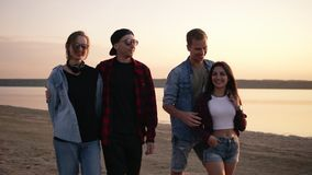 Enjoying life with best friends. Two beautiful young couples walking by the beach together in the evening dusk. Boys are. Hugging their girlfriends. Smiling stock video footage