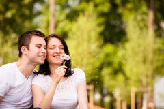 Enjoying life - couple blowing dandelions Stock Photo