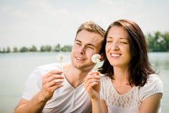 Enjoying life - couple blowing dandelions Stock Image