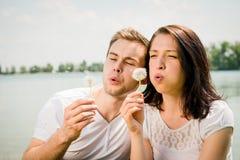Enjoying life - couple blowing dandelions Royalty Free Stock Image
