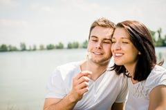 Enjoying life - couple blowing dandelions Royalty Free Stock Photo