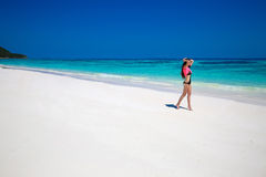 Enjoying life. Healthy woman walking on exotic sea. Fit brunette Royalty Free Stock Photos