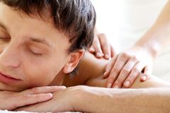 Enjoying massage. Portrait of calm guy enjoying the procedure of massage Royalty Free Stock Image