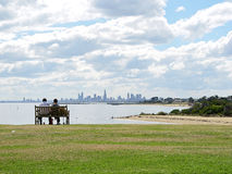 Enjoying the Melbourne skyline. Picturesque view of a couple sitting on a bench at Brighton Beach enjoying the view of Melbourne city horizon Royalty Free Stock Photos