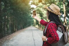 Enjoying moment woman backpacker and selfie in the road and forest background. Relax time on holiday concept travel ,color of vintage tone and soft focus Stock Photography