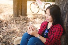 Enjoying moment woman using smartphone sitting under the big tree on park. Relax time on holiday concept ,color of vintage Royalty Free Stock Photo