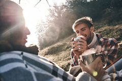 Enjoying morning together. Happy young couple having morning cof. Fee while camping in mountains Royalty Free Stock Photos