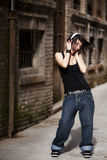 Enjoying music. Beautiful young girl enjoying music in urban alley Stock Photography