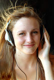 Enjoying music. A beautiful teen wearing headphones and listening to music with hair blowing Royalty Free Stock Images