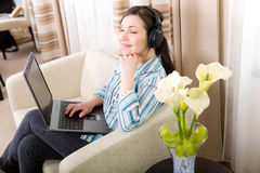 Enjoying music. Young adult woman relaxing at home stock image