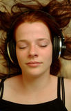 Enjoying music 2. A teenager with headphones lying on a sofa Royalty Free Stock Image
