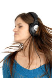 Enjoying music. A young woman closes her eyes and turns her head to the music she is listening on her headphones Stock Image