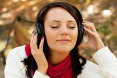 Enjoying music in autumn park Royalty Free Stock Photo