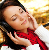 Enjoying music in autumn park Royalty Free Stock Image