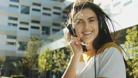 Enjoying the Music. Happy carefree woman wears headphones enjoying the music while walking along modern building stock footage
