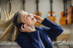 Enjoying Music At School. Teen student is enjoying listening to music on some headphones in her school music lesson. She is swaying to the beat and is laughing Royalty Free Stock Photography