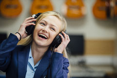 Enjoying Music At School. Teen student is enjoying listening to music on some headphones in her school music lesson. She is swaying to the beat and is laughing Stock Images