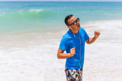 Enjoying music sports lifestyle happy young man in headphones walking on the sea shore Royalty Free Stock Image
