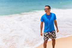 Enjoying music sports lifestyle happy young man in headphones walking on the sea shore Stock Photography