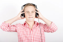 Enjoying music. Teenager listens music with headphones on light background Royalty Free Stock Photo