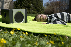 Enjoying music from wireless and portable speakers. Young boy laying on a blanket in the grass listening to music streaming frpm his smartphone to a wireless and Royalty Free Stock Images
